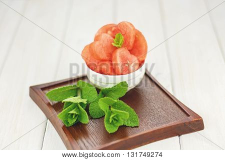 White bowl on a wooden board full of red hearts from watermelon