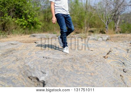 Boy Walking On The Rocky Land.