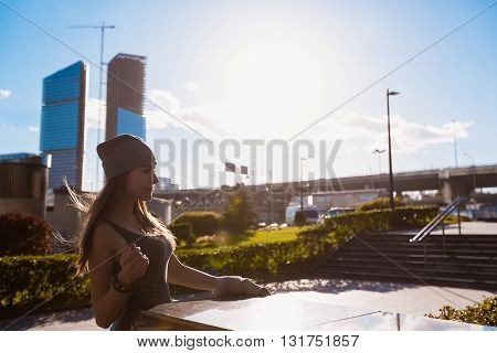 Young girl walking outdoors in a city on the background of skyscrapers