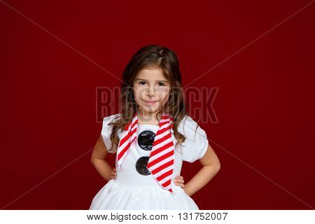 A cute brunette girl with curly hair and hands on hips stands with a confidet closed mouth smile for a portrait against a red background.