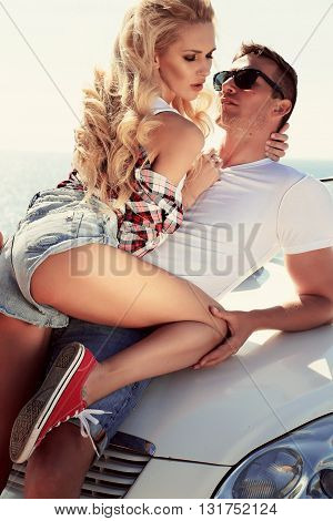 love story. fashion outdoor photo of impassioned couple in casual clothes, posing beside luxurious car