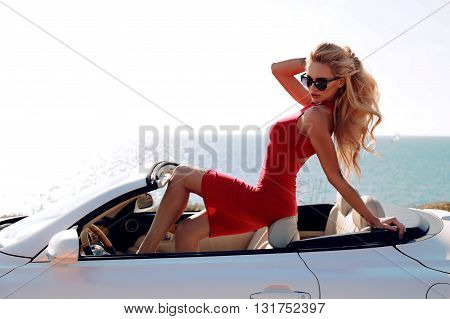 fashion outdoor photo of gorgeous sensual woman with blond hair in elegant red dress, posing beside luxurious auto