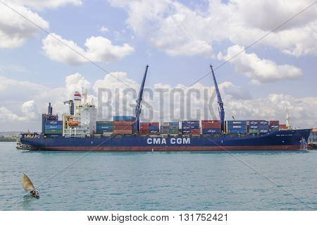 ZANZIBAR TANZANIA - JUNE 16: a small vessel sailing near a huge container ship in the harbor of Stone Town on June 16 2013 in Zanzibar. Stone town is one of the main harbor of Africa