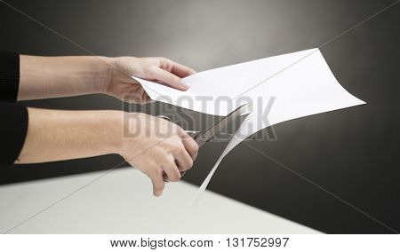 WOMAN'S HAND, CUTTING A WHITE PAPER, WITH SCISSORS  ON HIGHLIGHTED BLACK WALL BACKGROUND