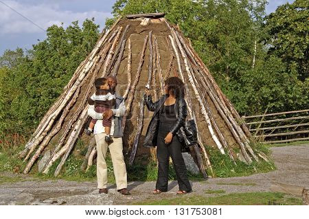 STOCKHOLM, SWEDEN - OCTOBER 01, 2006: Unidentified people near old hovel in Skansen, Stockholm, Sweden. Sami lived in the tents that covered the peat skins and fir bark. Skansen (the Sconce) is the first open-air museum and zoo in Sweden