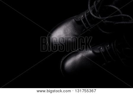 A pair of black army boots with shoe laces on black background