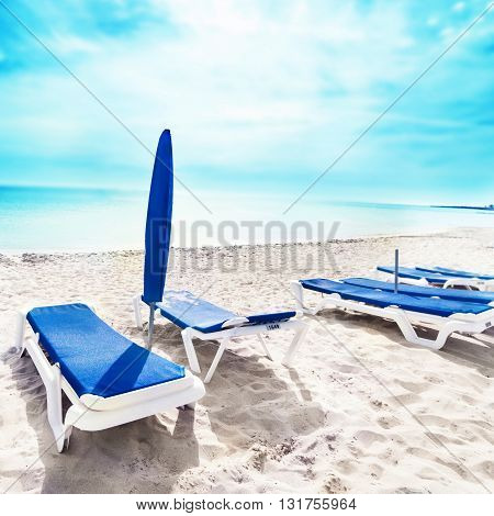 Vacation holidays background with beach lounge chairs and tents