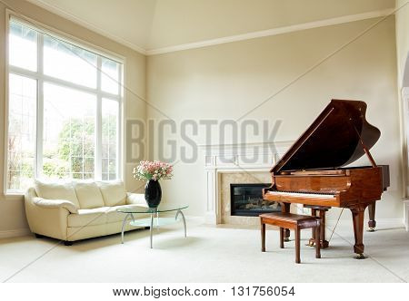Living room with grand piano fireplace sofa and large window with bright daylight coming through.