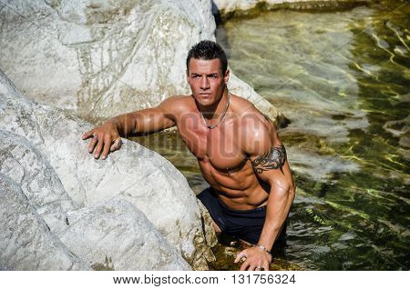 Handsome young muscle man standing in water pond or river