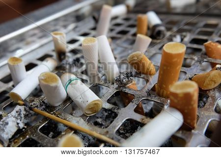 many left smoked cigarette butts fag-end in ashtray on no smoking day.