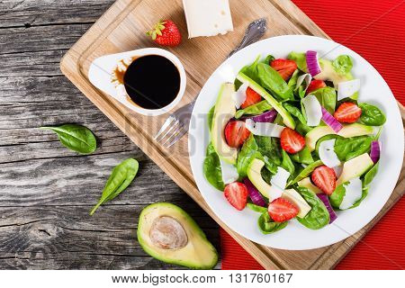 Strawberry baby spinach red onion goat cheese and avocado salad on a white dish on a cutting board close-up studio light