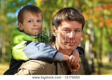 Happy father walking at the autumn park with his son.