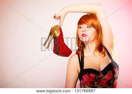 Shopaholic fashion and women style. Shopping time. Young red haired female holding high heeled shoes in hands on pink background. Studio shot.