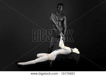 Passionate couple with bodies painted in white and black colors. Body painting project.