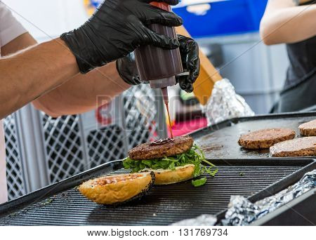 Chef preparing tasty burgers at outdoor stand. Street food photography.