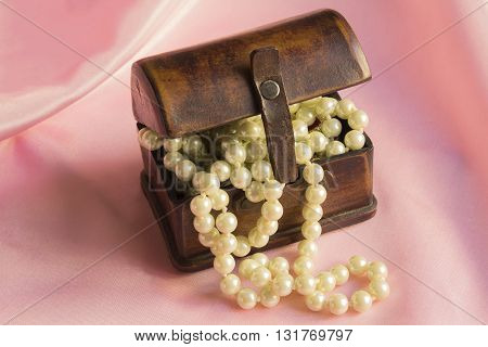 Pearl Necklace in an ancient casket on a pink silk