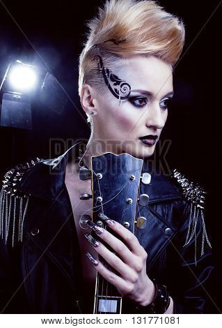 Fashion Rocker Style Model Girl Portrait. Hairstyle. Punk Woman Makeup, Hairdo and black Nails. Smoky Eyes in studio with guitar