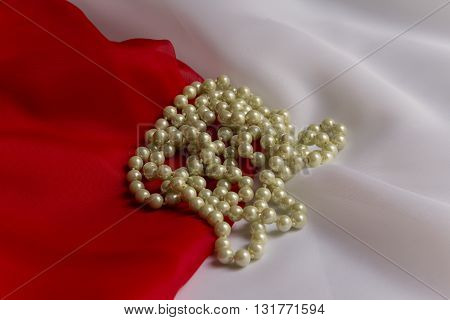 Pearl necklace on a background of delicate white and red silk