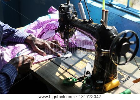 KUMROKHALI, INDIA - FEBRUARY 13: Man is working with sewing machine in Kumrokhali, West Bengal, India on February 13, 2014