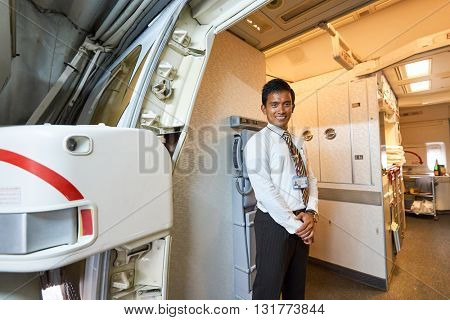 DUBAI, UAE - MARCH 09, 2016: Emirates crew member meet passengers on board of Boeing 777. Emirates is one of two flag carriers of the UAE along with Etihad Airways and is based in Dubai.