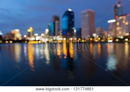 Abstract blurred lights night view, office building waterfront at twilight