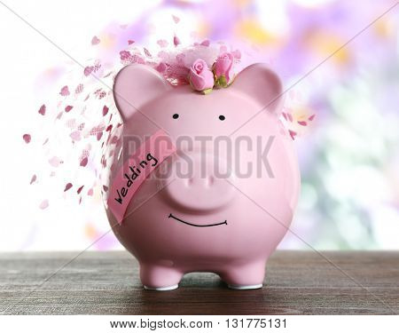 Piggy bank with wedding veil blurred festive background