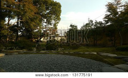 Garden of Antique Japanese house in Japan with rocks, plants, and trees.