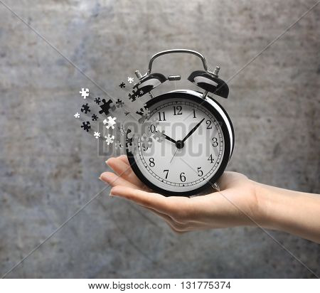 A retro alarm-clock on female hand on gray background. Lost time concept