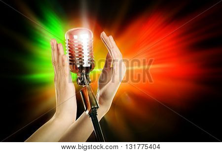 Retro microphone in female hands on laser rays background