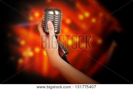 Retro microphone in female hand on laser rays background