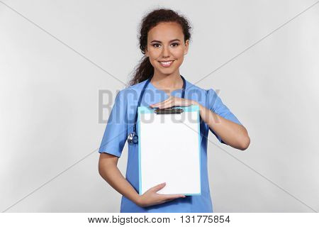 Beautiful African American female doctor on grey background