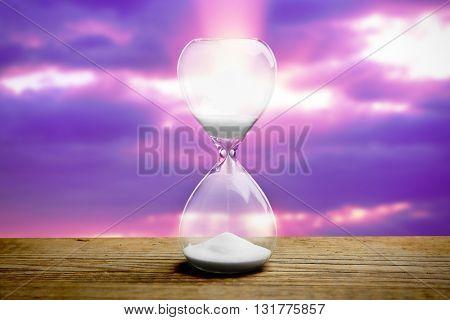 Hourglass on blurred purple sunset background
