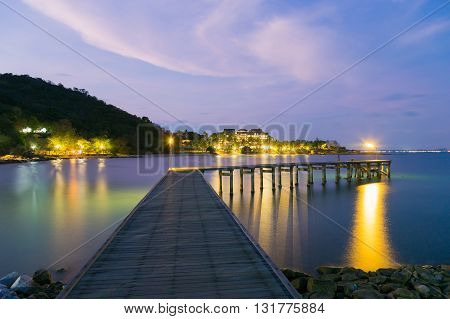 Wooden bridge walkway leading to the sea night view, with mountain background