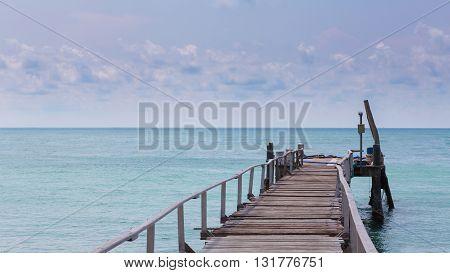 Long wooden bridge leading to ocean, natural skyline landscape background