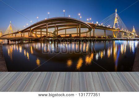 Opening wooden floor, Panorama Suspension bridge and highway at twilight and reflection