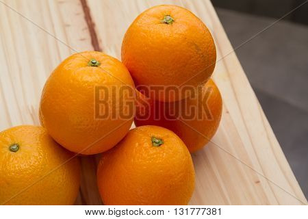 Oranges over a wood table on natural environment.