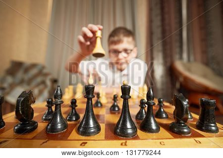 boy with glasses in a white shirt playing chess making a move holding the figure smiles