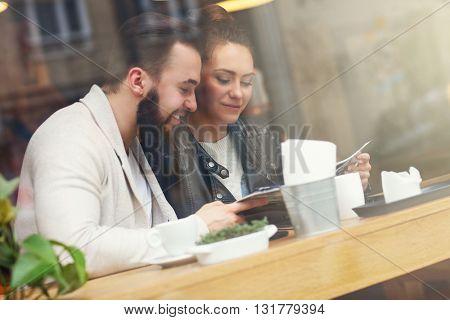 Happy couple choosing from menu in restaurant