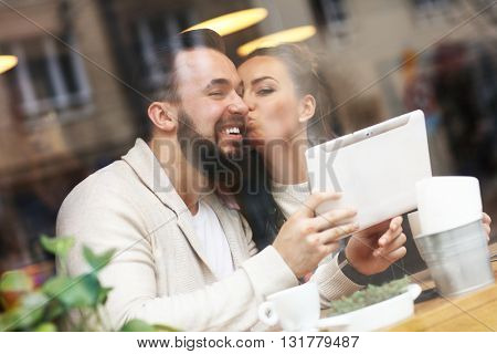 Picture of happy couple using tablet in restaurant