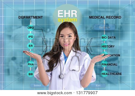 Female doctor stand in front of blue background of EHR system or electronic health record screen.