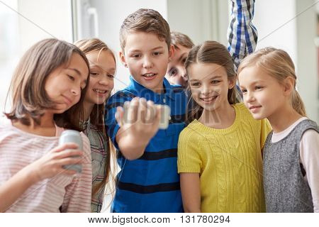education, elementary school, drinks, children and people concept - group of school kids with smartphone and soda cans taking selfie in corridor