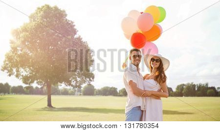 love, relations, holidays, dating and people concept - smiling couple wearing sunglasses with balloons hugging over summer park background