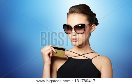 shopping, finances, fashion, people and luxury concept - beautiful young woman in elegant black sunglasses with credit card over blue background