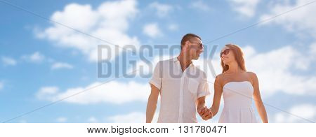 love, people and relations concept - happy couple wearing sunglasses walking over blue sky background