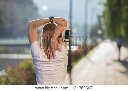 Fit blonde runner   woman warming up and stretching before morning jogging