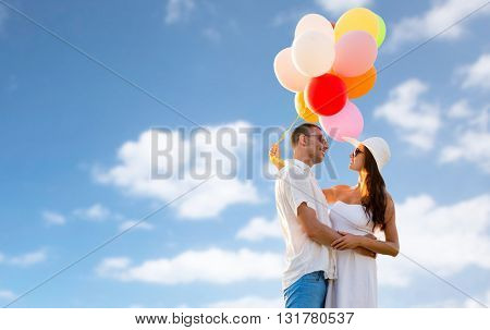love, holidays, summer, dating and people concept - smiling couple wearing sunglasses with balloons hugging over blue sky background