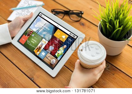 business, mass media, technology, people and advertisement concept - close up of woman with internet news application on tablet pc computer screen and coffee cup on wooden table