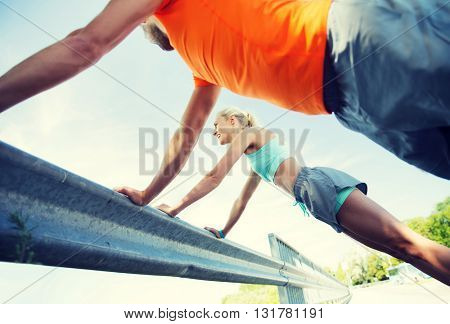 fitness, sport, training and healthy lifestyle concept - close up of happy couple doing push-ups outdoors
