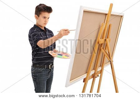 Little kid painting on a canvas with a paintbrush isolated on white background