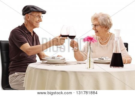 Elderly couple making a toast with red wine on a romantic date isolated on white background